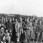 Генерал Дража Михаиловић са западнобосанским четницима, октобра 1944. у Требави. Десно од Драже је пуковник Славољуб Врањешевић, а лево је амерички пуковник Роберт Мекдауел. Клечи, са тамним наочарима, амерички капетан Никола Ник Лалић