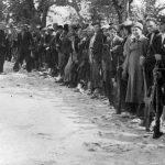 Дрварско-петровачки четнички одред у Книну 1942. године. Активни артиљеријски поднаредник Миле Богић ''Тобџија'', командир чете, стоји сасвим лево, има црну шајкачу (погинуо је 12. јула исте године у с. Казанци у борби против комуниста). Испред Богића, има светлу шајкачу, стоји активни жандармеријски наредник Бранко Торбица, командант 3. батаљона 1. босанског пука ''Гаврило Принцип'' (погинуо 14. јануара 1943 у Грачацу у борби против комуниста). Испред Торбице, у раскораку, је Миле Кецман (погинуо на Пађанима 3. децембра 1944, у борби против комуниста). У средини реда, насмејан и нагнут напред Божидар Божо Томић (живи у Милвокију, САД). Други десно од Томића је Симо Бурсаћ, један од петорице првих устаника 26. јула 1941. године у Дрвару  Стоји трећи с десна, држи митраљез, Никола Ћук. Током 1943. био је командант Петровачког четничког одреда, а потом Далматинске свилајске бригаде Динарске четничке дивизије (Живи у Аустралији). Са Ћукове десне стране је Мићо Јојић (заробљен од комуниста 16. септембра 1942. и стрељан у Тичеву код Дрвара