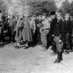 Народ дочекује Дражу и америчке официре у селу Кожухе код Добоја, октобра 1944. Са десне стране, гледа у камеру, је Васо Вуковић, трговац, оснивач четничке организације у селу пре рата. Године 1941. на челу устаника у селима Кожухе, Копривна и Врањак