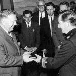 Хамилтон, Канада, 21. маја 1966. године. Краљ Петар II уручује Орден ратног крста-споменице 1941-1945. Љубисаву Љуби Раонићу. Раонић је рођен 1905. у селу Статовац код Прокупља. Припадао је Другој топличкој бригади Топличког корпуса. Наредбом генерала Михаиловића од 1. децембра 1944. унапређен је у чин потпоручника, а похвалном наредбом од 3. фебруара 1945. одликован је Златном медаљом за храброст Обилића. Живи у Хамилтону