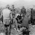 Родбина ставља у сандук леш извађен из јаме. Изнад Жупе Никшићке, 1942. године