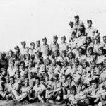 Логор Еболи, 28. јула 1946. године. Друга чета Првог батаљона Дринског пука Југословенске војске ван Отаџбине. Означен са I је командант пука мајор Петко Лаковић (у рату командант бригаде у области Златибора и Пожеге), под II је помоћник команданта пука капетан М. Константиновић (током рата у заробљеништву), под III је командант Првог батаљона мајор М. Анастасијевић (у рату код Недића, у Босни са четницима), под IV је командир Друге чете потпоручник Јово Недељковић (у рату командант бригаде у Млавском корпусу), под V је потпоручник Живко Милинковић (у рату командант батаљона у Млавском корпусу), под VI је потпоручник Ратко Живковић (у рату у Церско-мајевичкој групи корпуса) и под VII је поручник Драгомир Живановић (у рату у Јастребачком корпусу)
