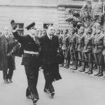 """Младен Лорковић (десно) и Зигфрид Каше у Загребу маја 1941. године. Лорковић, правник по професији, постао је усташа још 1934. године; важио је за германофила и великог србомрсца. Један је од петорице потписника изјаве од 30. марта 1941. којом се захтева немачка помоћ у успостављању самосталне хрватске државе. Павелић га 9. јуна 1941. именује за министра спољних послова. У априлу 1943. био је умешан у аферу око кријумчарења злата, због које је шеф његовог кабинета Иво Колак осуђен на смрт. Дана 28. априла разрешен је дужности министра спољних послова. Именован је за државног министра без ресора, задужен за послове са немачком војском. Када су немачка ратна кола кренула низбрдо покушао је уз помоћ ХСС-а да ступи у преговоре са Западним савезницима и обезбеди прелаз """"НДХ"""" на победничку страну. За ове преговоре знао је и Павелић кога је сам Лорковић обавестио. Међутим, августа 1944. године, Павелић га избацује из владе и ставља под суд, под изговором """"завере против поглавника и немачких савезника"""". Ухапшен је и затворен у Копривници, а одатле је пребачен у Лепоглаву, заједно са министром оружаних снага Антом Вокићем и другим присталицама промене курса """"НДХ"""". Сви су побијени у Лепоглави од стране усташа крајем априла 1945. године, непосредно пре Павелићевог напуштања Загреба. Каше је био члан Национал-социјалистичке радничке партије од 1926. године. Постављен је 20. априла 1941. године за посланика Трећег Рајха у нацистичкој Хрватској. Важио је за ватреног присталицу усташког режима, не само због идеолошке блискости, већ и због редовне, месечне """"дозе мита"""" коју му је усташка влада уплаћивала на један тајни рачун у швајцарској банци. Маја 1945. године побегао је у Аустрију, одакле је враћен Југославији. Осуђен на смрт као ратни злочинац и обешен 7. јуна 1947. године."""