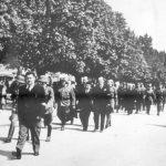 Снимљено у Бањалуци лета 1941. На челу колоне је Виктор Гутић, Павелићев повереник за Босанску Крајину, организатор злочина над Србима у овој области. На протесте Немаца због Гутићевих зверстава, Павелић га повлачи из Бањалуке. После рата изручен Југославији из Италије и као ратни злочинац ликвидиран у Сарајеву 1946. године