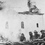 """Хрвати """"позирају"""" испред спаљене цркве Света Недеља у Војнићу."""