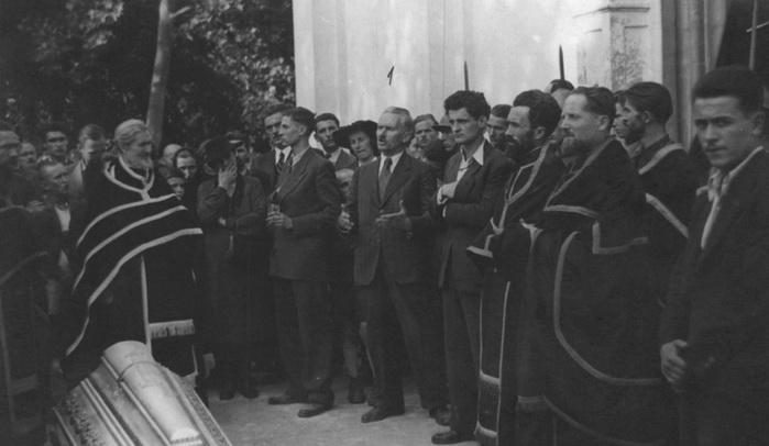 Димитрије Љотић држи говор на сахрани распопа Булића, испред цркве у Чачку. Са његове леве и десне стране стоје телохранитељи, са рукама на дршкама револвера у унутрашњим џеповима. Овакве мере предострожности су биле неопходне због непопуларности како самог Љотића тако и његовог покрета.