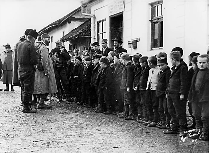 Дража обилази школу у Коштунићима. Иза њега је др Топаловић, лево се види др Ђуровић, а десно капетан Вучковић