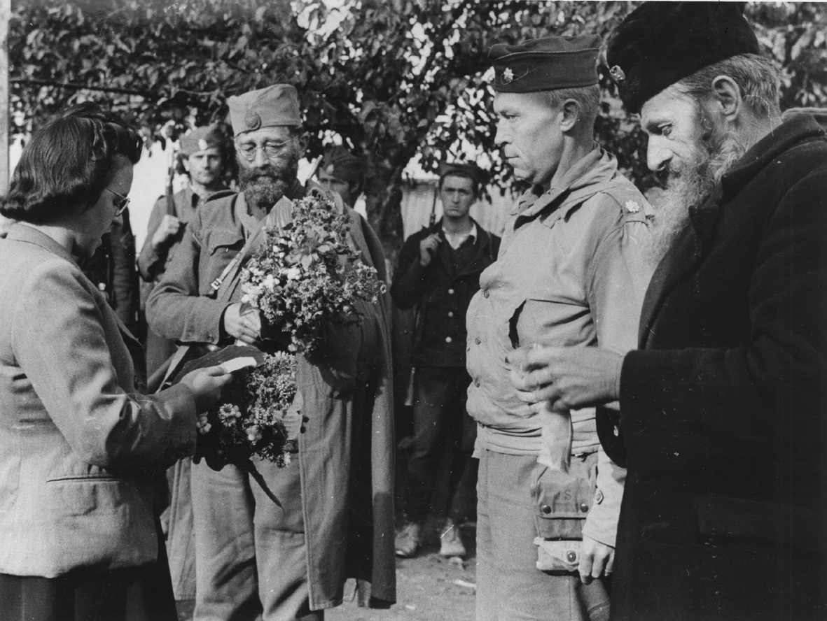 "The Serbian people receiving General Mihailovich in a village in Doboj in Northern Bosnia and Hercegovina, October 1944. General Draza Mihailovich is receiving the flowers from the young lady and American Lieutenant Colonel Robert H. McDowell of the OSS ""Ranger Mission"" is standing to the left of Mihailovich, holding the general's coat."