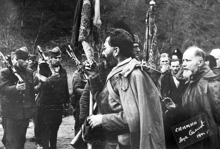 Село Ба, на Св. Саву 1944: Дража љуби ратну заставу из Првог светског рата. Иза њега је академик рез. пуковник Драгиша Васић