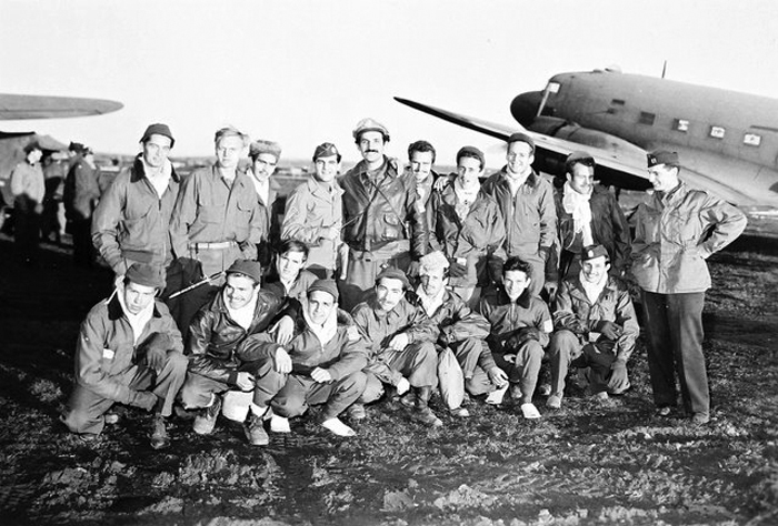 "Final Evacuation of Allied Airmen from Yugoslavia, December 27, 1944. Standing far right is Major George Vujnovich, OSS Chief of the Halyard Mission. Also pictured is Captain Nick Lalich, standing center in bomber jacket, and Arthur ""Jibby"" Jibilian, center,  kneeling in front of Lalich, both of the OSS, and both integral to the epic successful Halyard evacuations."