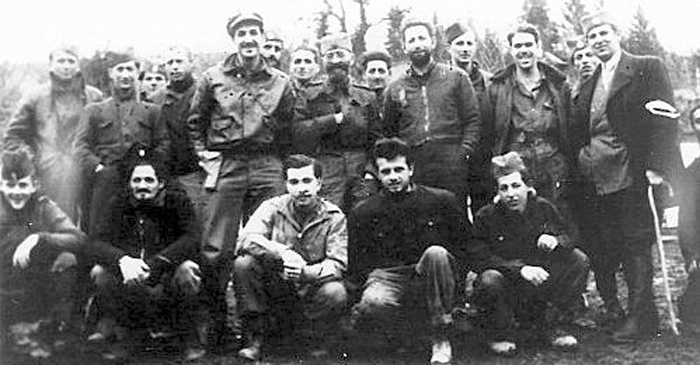 Gen. Draza Mihailovich standing with his hand over his heart  in the middle row, with Serbs and American airmen.  Nick Lalich is to Draza's right and  Arthur Jibilian is in the front row between them. December 1944.
