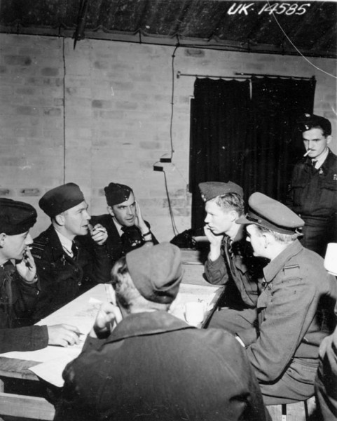 The debriefing of aircrew after a bombing sortie: a site familiar to Bomber Command veterans. This photo shows personnel from No. 433 (Porcupine) Squadron, RCAF, after a raid on German flying-bomb sites in France, 1944. Library and Archives Canada, Faces of War, Unknown Photographer.