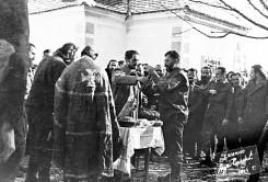 Горња Оровица изнад Љубовије, 19. децембра 1943. Дража прославља своју крсну славу, Св. Николу. Свећу пали капетан Предраг Раковић. Трећи с лева стоји мајор Аћим Слејепчевић (крсти се), четврти потпуковник Лалатовић, а између њих, иза, је мајор Филиповић